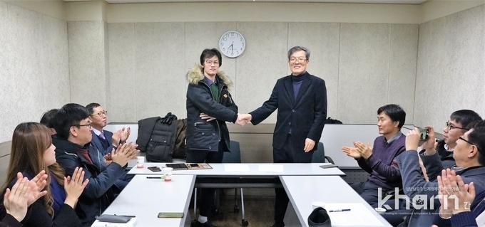 박종원 회장(우)과 이일영 회장이 통합을 선언하고 악수하고 있다.
